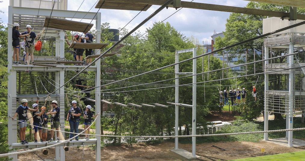 Students attempting the ropes challenge course