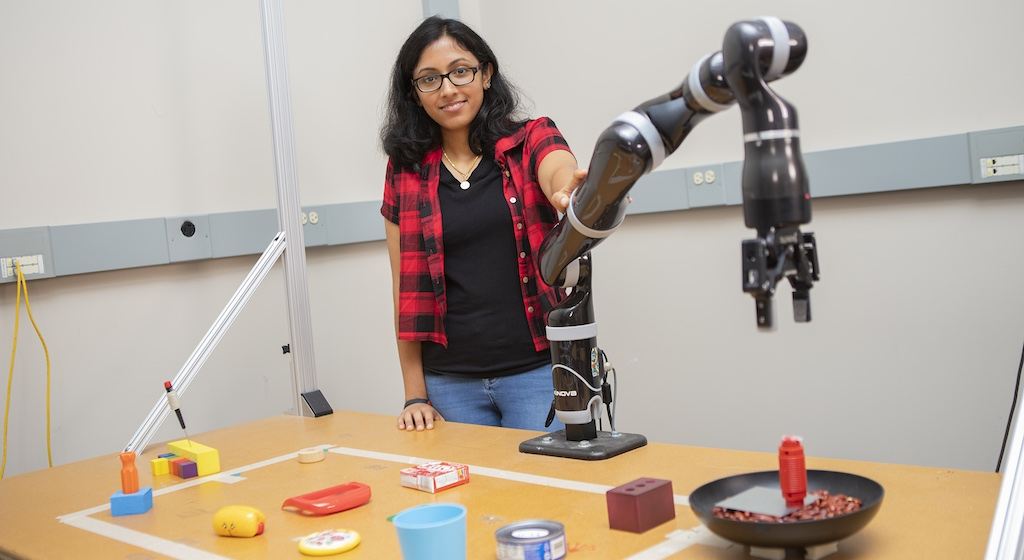 Lakshmi Nair poses with her robotic arm and assorted parts on a table used to create simple tools.